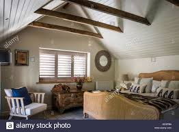 plantation shutters and white wooden ceiling cladding in attic plantation shutters and white wooden ceiling cladding in attic bedroom with vintage french cane bed