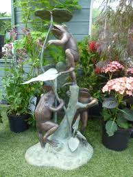 bronze statue of three frogs on water water feature in