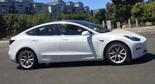 white tesla model 3 spotted in traffic all design lines visible
