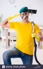 Cleaning The House by Funny Man In Military Style Cleaning The House Stock Photo