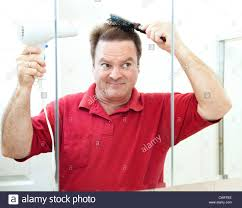 mature man blow drying his hair in the bathroom mirror stock photo