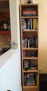 free standing white wooden book case with tall swing glass door