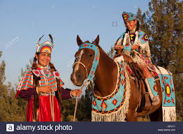 native american family of two sisters dressed in traditional
