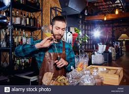 bartender hipster with a beard makes an alcoholic cocktail behind