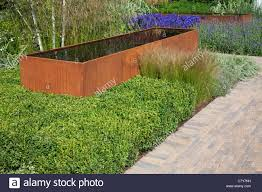 contemporary garden with rusted corten steel water trough and