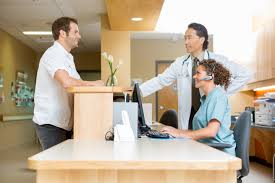 Doctor And Nurse Patient With Doctor And Nurse At Reception Desk Jellyfish Health