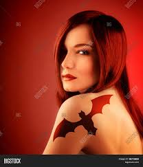 halloween red background photo of beautiful with bat tattoo on shoulder isolated