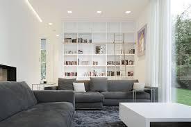 spacious living room design with high white bookcase and dark grey