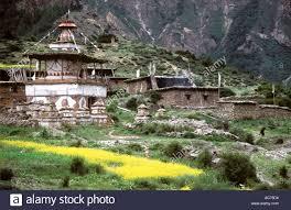 tibetan buddhist chortens and farm houses with prayer flag poles