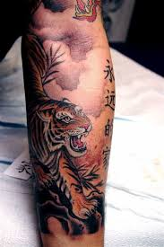 colorful gnarling tiger and hieroglyphs on forearm