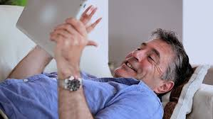 Mature Man Lying On The Couch Using Tablet Pc At Home In The - Lying sofa 2