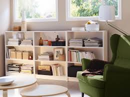 basement living room with three low billy bookcases in white and a