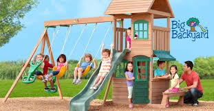 exterior back yard wooden swing set on green lawn stock photo
