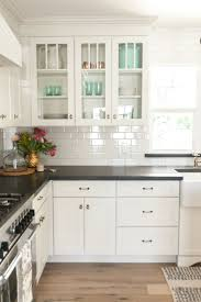 Ceramic Tile With Glass Backsplash White Kitchen Cabinets Black Countertops And White Subway Tile With