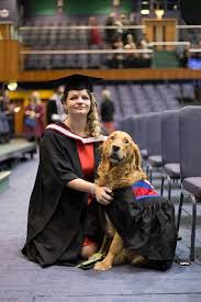 dog graduation cap and gown owner and dog graduates in graduation cap and gown