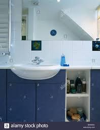 basin set into blue vanity unit below mirror in modern white