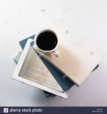 a cup of coffee on top of a pile of books and a tablet stock photo