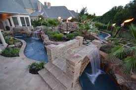 large backyard lazy river pool design with rock and garden with lounge area in the middle plus bridge with waterfall ans stone floor tiles ideas