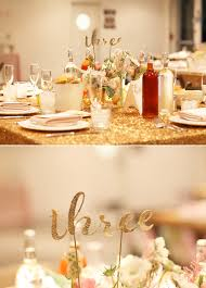 gold wedding table numbers paper cut out table numbers and gold sparkle linens photo by