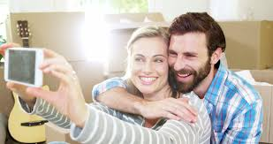 young couple laughing watching movies in bed on digital tablet