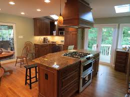 Kitchen Island Layouts And Design by Wooden Kitchen Island With Modern Stove Top On Glossy Brown Marble