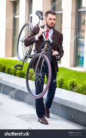 handsome businessman carrying his bicycle on stock photo 289837076 handsome businessman carrying his bicycle on city streets the concept of the modern lifestyle of