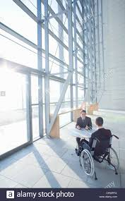 businessman in wheelchair meeting with co worker in modern lobby