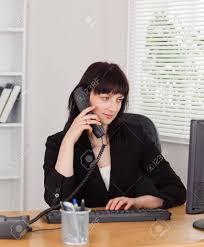sur le bureau femme brune sur le téléphone tout en travaillant sur un