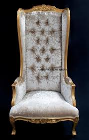 a gold ornate high back porters arm chair in gold leaf and mercury