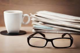 sur le bureau lunettes tasse de café et pile de journaux sur le bureau en bois