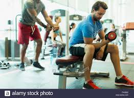 man doing dumbbell biceps curls at gym stock photo royalty free