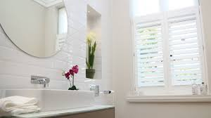 half height waterproof plantation shutters installed in a bathroom
