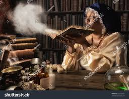 medieval alchemist blowing dust off old stock photo 155157932
