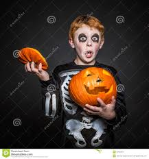 kid halloween background surprised red hair kid in halloween costume holding a orange
