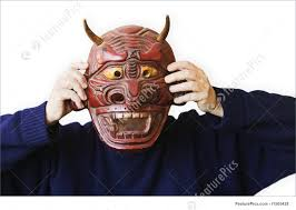 halloween person holding up a devil mask stock picture i1565428