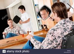 man looking himself in a mirror after a haircut stock photo
