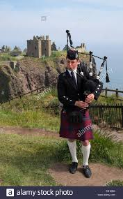piper playing pipes in traditional scottish kilt at dunnottar