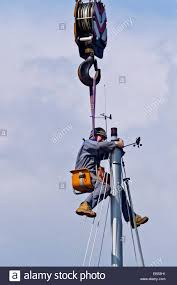 workman seated in bosun u0027s chair suspended from a crane working at