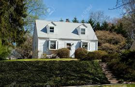 Single Family Home by Modest Clapboard Cape Cod Style Single Family Home In Suburban