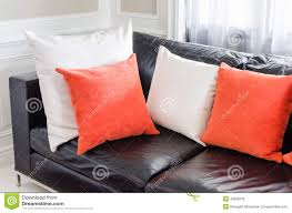 Orange Pillows For Sofa by Orange And White Pillows On Modern Black Sofa In Stock Photo