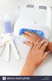 hands with uv lamp for nails stock photo royalty free image