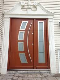 brown wooden door with curving glass ornaments also high windows