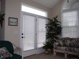 decorating glass door and window with white faux wood blinds on