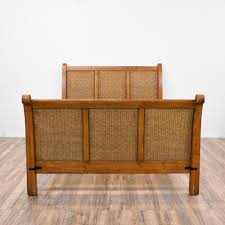 this tropical bed frame is featured in a solid wood with a glossy