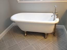 bathroom white clawfoot tub with tile flooring and glass window