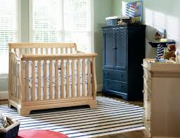unfinished sleigh crib placed in the nursery room with stripes