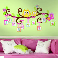 lovely unisex kids room with pink bed and white cushions and green wall decor