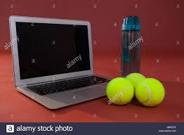 up of fluorescent yellow tennis balls by laptop and water