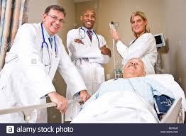 recovery room nurse doctors and nurse with patient in recovery room stock photo