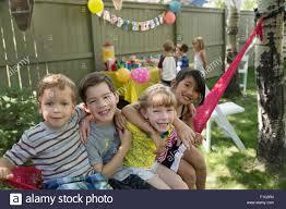 portrait smiling kids hammock backyard birthday party stock photo